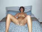 The Wife on the bed with her legs open showing her naughty bits