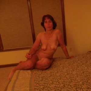 The Wife sitting naked on the bed waiting for The Husband