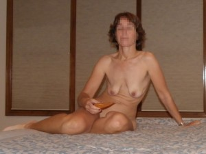 The Wife sitting naked on the bed with some flavored lubricant waiting for The Husband