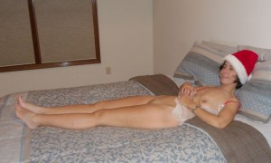 The Wife relaxing on the bed in a naughty Santa outfit