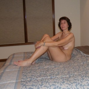 The Wife sitting on the bed waiting for The Husband