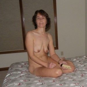 The Wife sitting naked on the bed with a tube of flavored lubricant waiting for The Husband