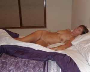 The Wife lying naked on the bed waiting for The Husband to join her