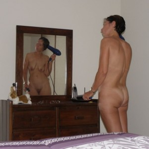 The Wife drying her hair in front of the mirror