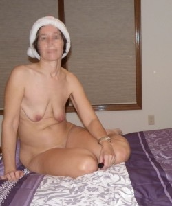 The Wife sitting naked on the bed wearing a Santa Hat