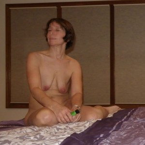 The Wife sitting naked on the bed with a tube of flavored lubricant