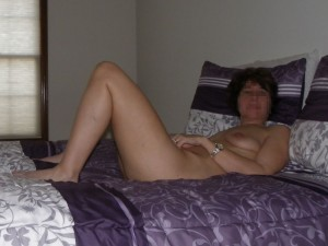 The wife relaxing naked on the bed on a bright spring day