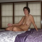 The Wife sitting naked on the bed with some flavored lubricant in her hand