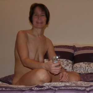 The Wife sitting naked on the bed waiting for The Husband with some flavored lubricant