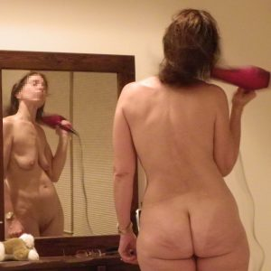 The Wife standing naked in front of the mirror drying her hair