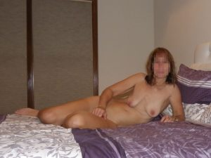 The Wife sitting naked on the bed before a photo session