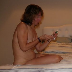 The Wife sitting naked on the bed with some flavored lubricant